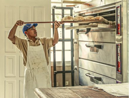 An image of a man in a bakery with an apron putting food into an oven, representative of the fact that only relevant information should go in a resume certifications section.